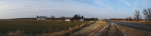Panorama of a small town farm in Kansas. Field, barn, railroad tracks and a blue sky.