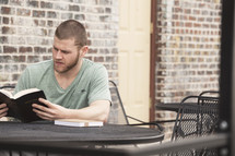 man reading a Bible sitting at a table at an outdoor cafe