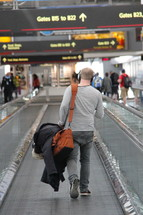 man carrying luggage on an airport travelator going on a journey