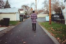 a man walking on a neighborhood street