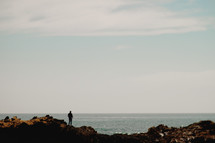 Man standing on a rock at a shore | Facing Forward | Overlooking | Vision | Beach | Background | Prayer | Sky