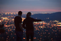 A couple looking out over the suburbs below at night.