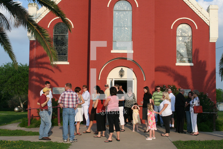 congregation gathered in front of a red church