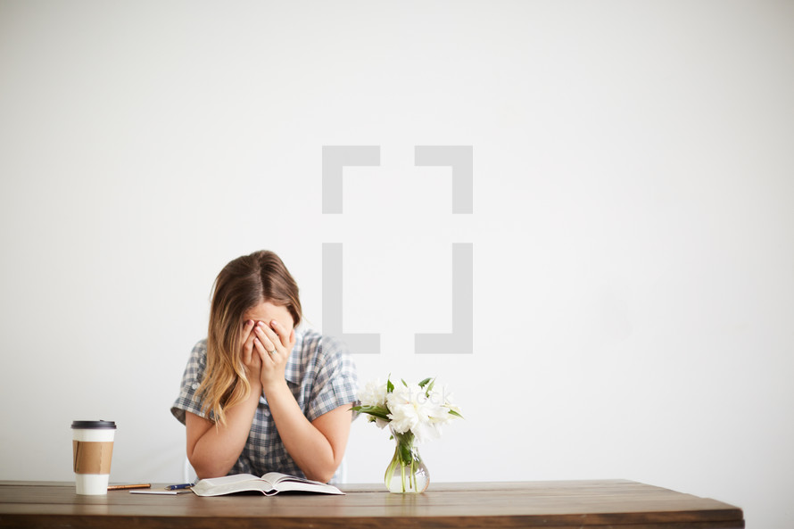 a woman covering her face over an open Bible