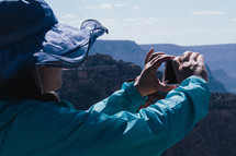 A woman in a hat taking a picture of the Grand Canyon.