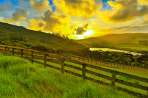 sunrise over a green pasture and fence line