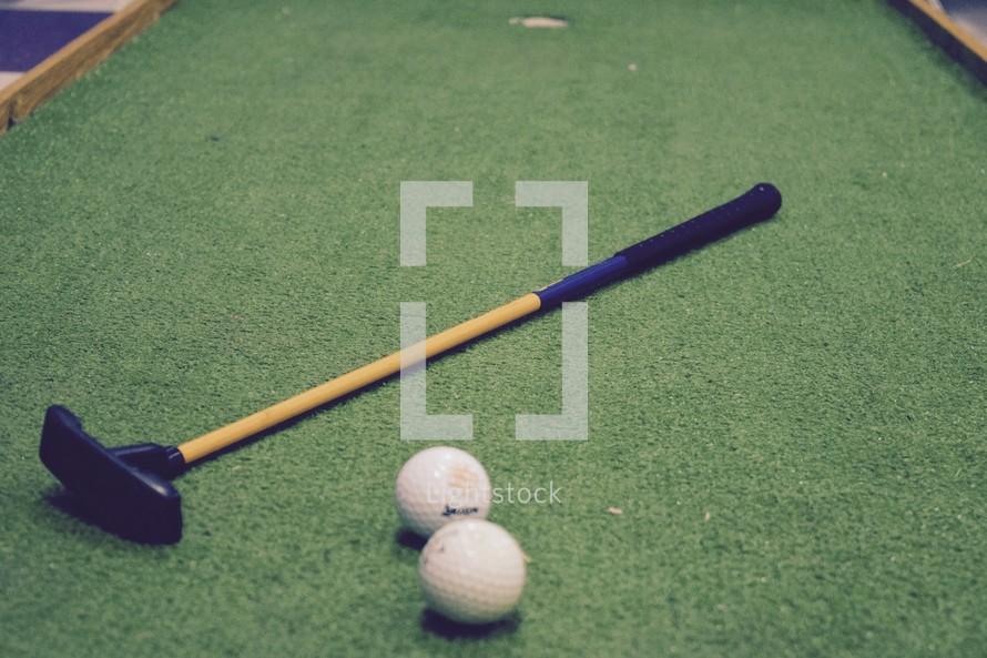 putt putt with golf balls and putter
