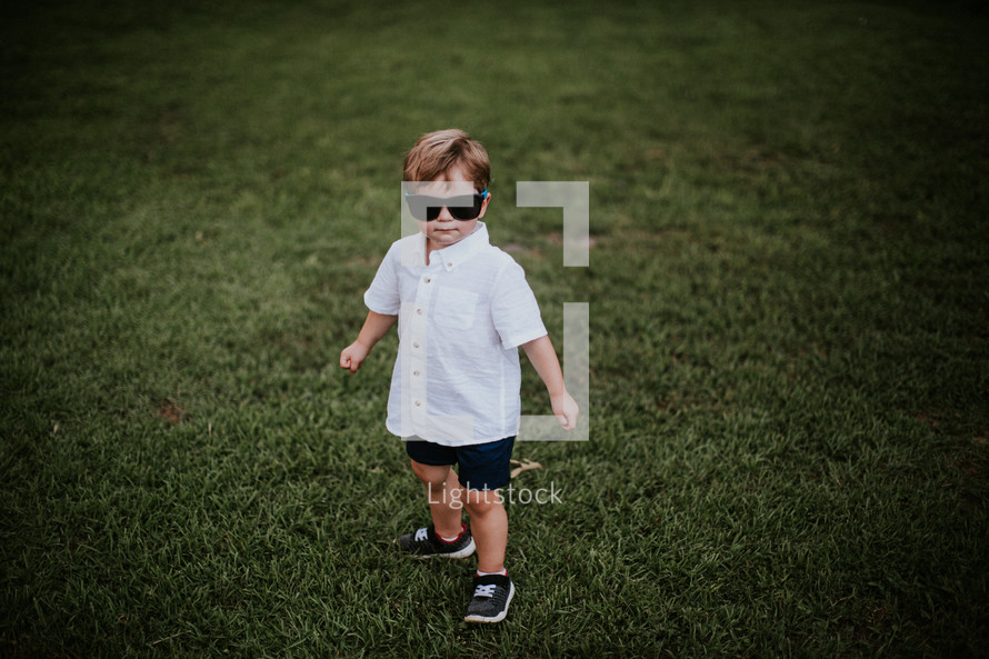 toddler in grass wearing sunglasses