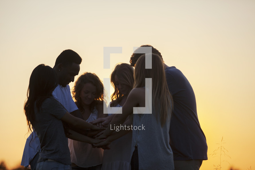 prayer circle outdoors at sunset