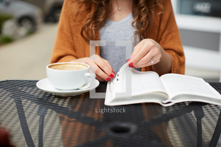 a woman sitting at an outdoor table reading a Bible