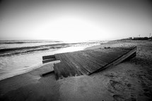a washed up pier on a shore