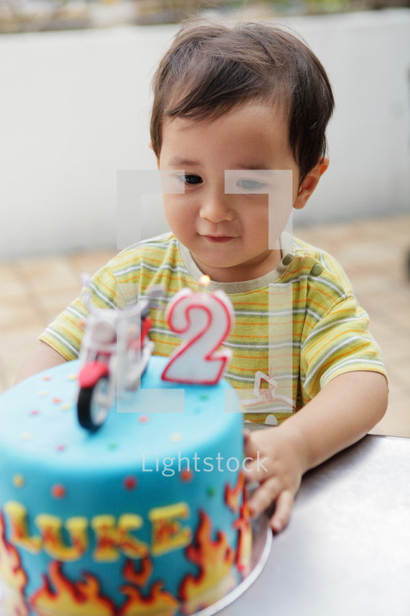 Cute Asian toddler boy blowing the candle on his cake