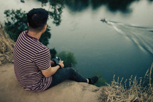 a man with a camera sitting at the edge of a cliff looking out at water below