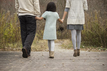 Family holding hands, walking across a wooden bridge outside.