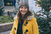 a young woman in a coat and beanie standing in front of a Christmas tree