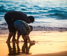 father and son digging in the sand on a beach
