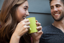 A young man and woman smiling at each other and drinking coffee.