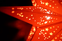 Light shining through a red paper star lantern.