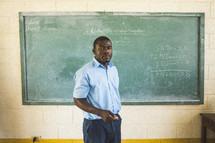 Teacher in front of a chalkboard in a classroom.