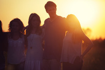 friends standing outdoors embracing at sunset