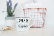 Journey message on a coffee mug, wire basket, and lavender house plant