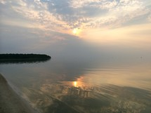 reflection of clouds on lake water at sunrise