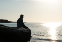 a man sitting on rocks thinking at the coast