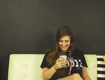 teen girl reading a text message on her phone