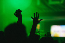 silhouettes of raised hands in an audience