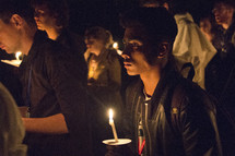holding candles at a worship service