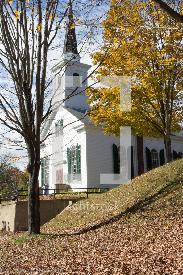 Church surrounded by fall foliage and fallen leaves,