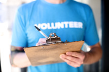 "Person writing on a clipboard wearing a blue shirt with the word, ""volunteer."""