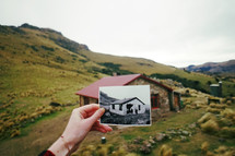 a woman holding up an old picture of a cabin in front of the present day cabin