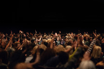 a crowded audience with hands raised at a concert
