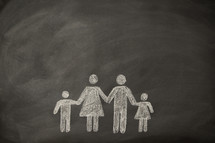 A simple drawing on a chalkboard of a family holding hands.