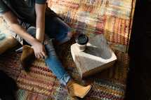woman sitting on a rug and a cup of coffee