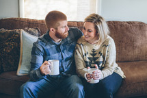 couple sitting on a couch drinking hot cocoa together