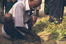 Squatting man weaving twigs and limbs in the dirt.