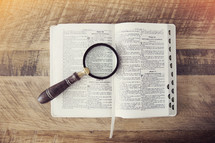 a magnifying glass over the pages of a Bible
