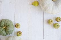 pumpkins, apples, and pears on white wood boards