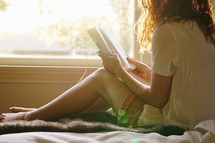 teen girl sitting on a bed reading a Bible