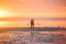 a couple hugging on a beach at sunset