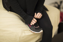 A woman tying her shoe in her house. Getting ready for a run.
