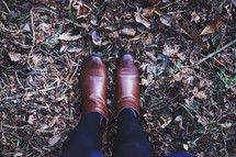 woman in boots standing in fall leaves