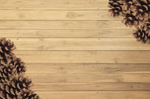 pine cones in corners on wood boards