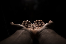 outstretched hands in darkness.