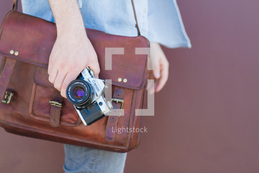 A man carrying a leather satchel and a camera.