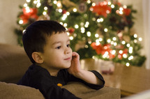 child near a Christmas tree