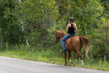 women riding a horse along the side of a country road
