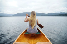 a woman paddling a canoe